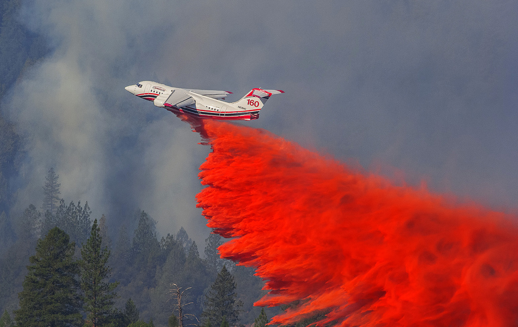 A firefighting aircraft drops retardant over a wildfire along a hillside near Foresthill, Calif. on October 9, 2014.