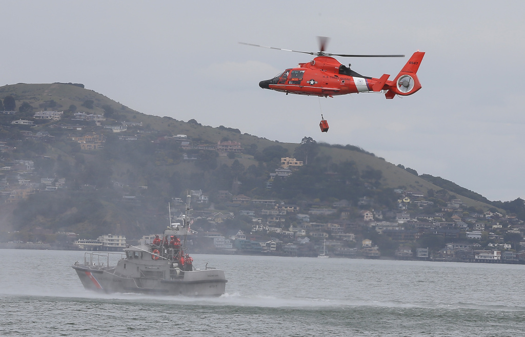 A U.S. Coast Guard HH-65 Dolphin helicopter participates in a drill with a 47 foot Coast Guard boat on March 7, 2013 in San Francisco, California. The U.S. Coast Guard has given up the search for a 43-year-old man swept to sea during a baptism ceremony on a Southern California beach.