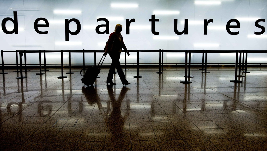 A woman pulls her suitcase as she walks through the departures area of Glasgow Airport in Glasgow, Scotland on May 5, 2010.