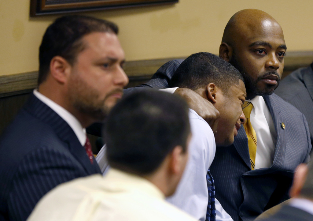 Defense attorney Walter Madison, right, holds his client, 16-year-old Ma'Lik Richmond, second from right, while defense attorney Adam Nemann, left, sits with his client Trent Mays, foreground, 17, as Judge Thomas Lipps pronounces them both delinquent on rape and other charges after their trial in juvenile court in Steubenville, Ohio, Sunday, March 17, 2013. Mays and Richmond were accused of raping a 16-year-old West Virginia girl in August 2012.