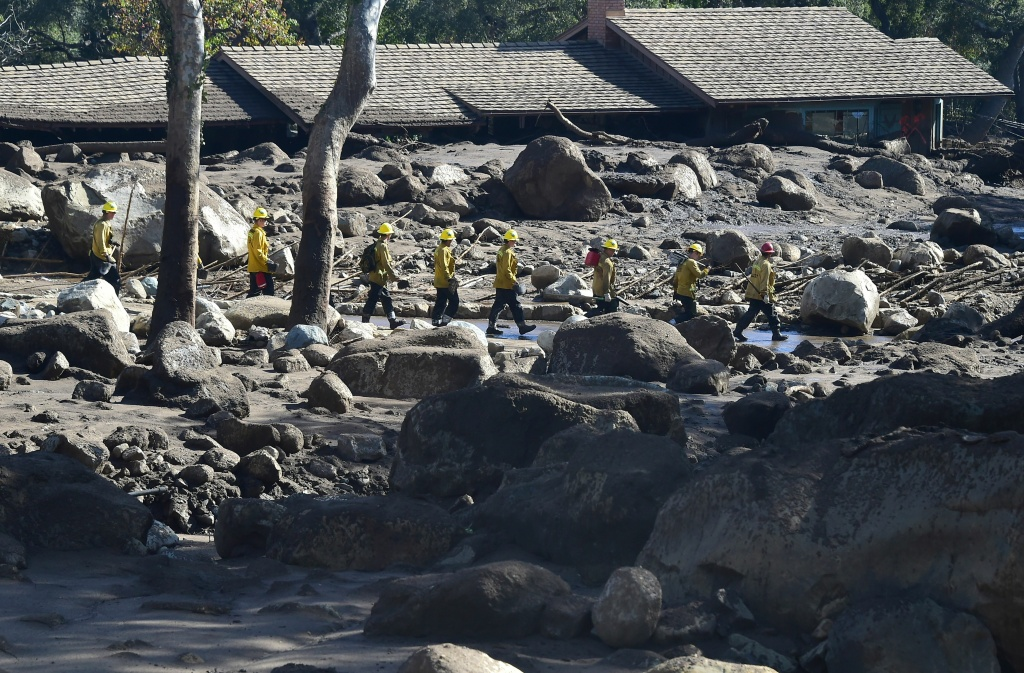 A firefighting handcrew walks past debris near a property buried in mud in Montecito, California January 12, 2018.