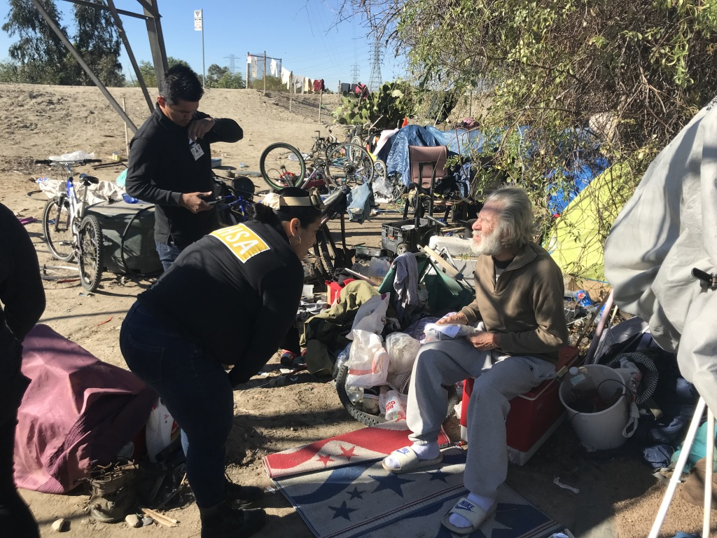 Outreach workers from the Los Angeles Homeless Services Authority speak to a homeless man living in an encampment in the San Gabriel River Valley in El Monte.