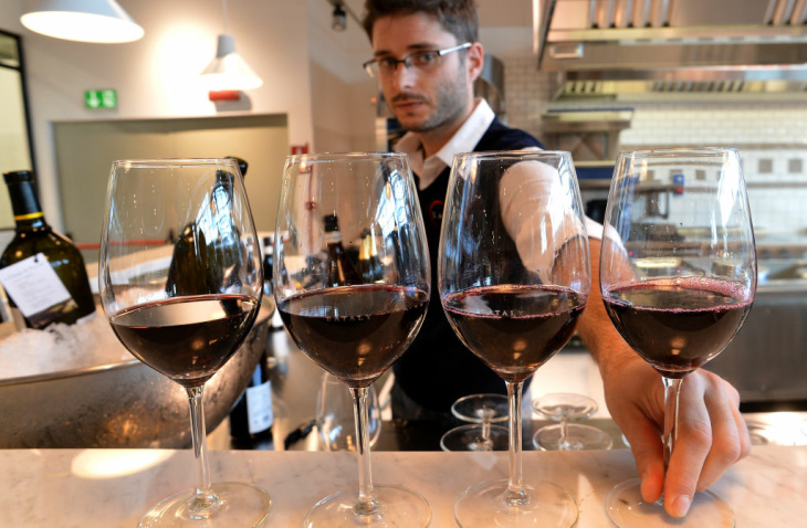 An employee serves Italian red wine at a counter of the Eataly food emporium on June 12, 2012 in Rome. The huge 17000 square meter Italian food and wine market, which is part of the international 'slow food' movement with branches in Japan and new York, will open its doors on June 21.