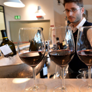 An employee serves Italian red wine at a