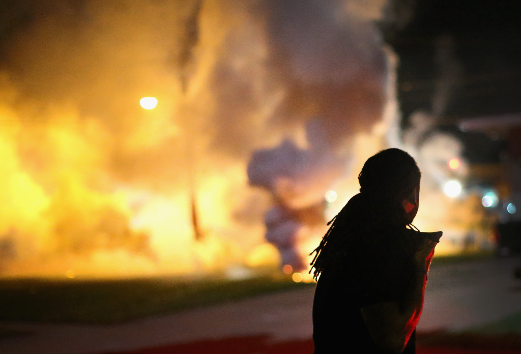 A demonstrator, protesting the shooting death of teenager Michael Brown, scrambles for cover as police fire tear gas on August 13, 2014 in Ferguson, Missouri. Brown was shot and killed by a Ferguson police officer on Saturday. Ferguson, a St. Louis suburb, is experiencing its fourth day of violent protests since the killing.
