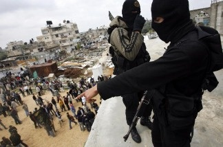 Two Islamic Jihad militants watch over a crowd from atop a mosque.