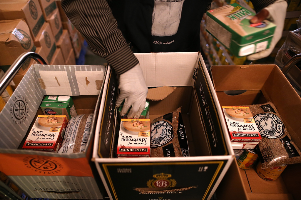 Richmond Emergency Food Bank volunteer Abdul Olorode packs boxes with food to be handed out to needy people on November 1, 2013 in Richmond, California.