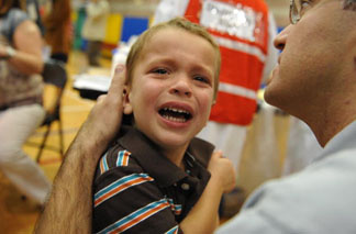 Three-year-old Daniel Abrams is comforted by his father after he received a vaccine shot on October 23, 2009 at the Balboa Sports Complex in Encino, California.