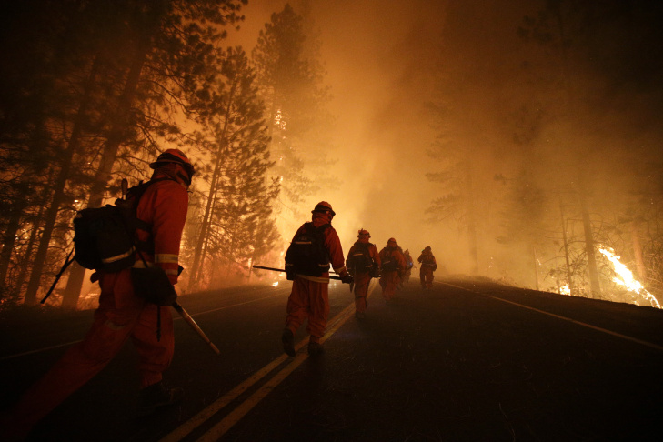 Inmate firefighters walk along Highway 120 as firefighters continue to battle the Rim Fire near Yosemite National Park, Calif., on Sunday, Aug. 25, 2013. Fire crews are clearing brush and setting sprinklers to protect two groves of giant sequoias as a massive week-old wildfire rages along the remote northwest edge of Yosemite National Park.