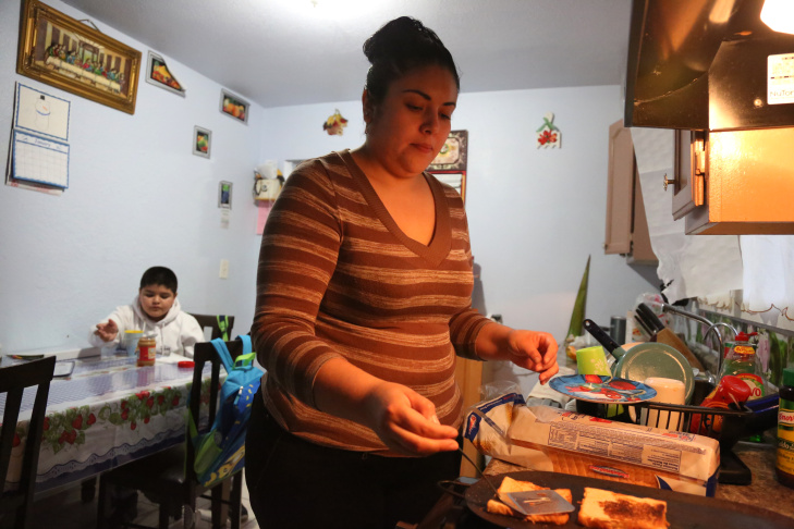 Maria Bernal, 30, cooks breakfast for her son Edwin Bernal, 9, before school at their home in Los Angeles. Edwin is among a group of children in the U.S. illegally who qualified for Medi-Cal coverage through a state-funded program.