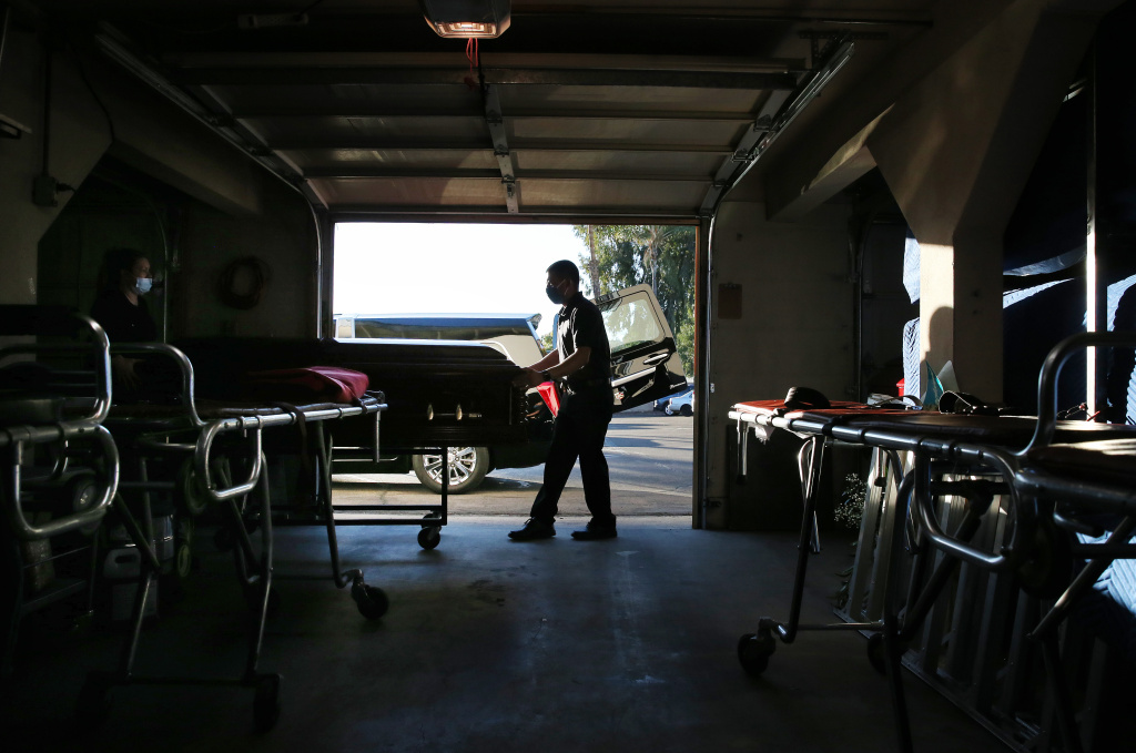 Funeral attendant Sam Deras helps wheel the casket of a person who died after contracting COVID-19 past gurneys toward a hearse at East County Mortuary on January 15, 2021 in El Cajon, California.