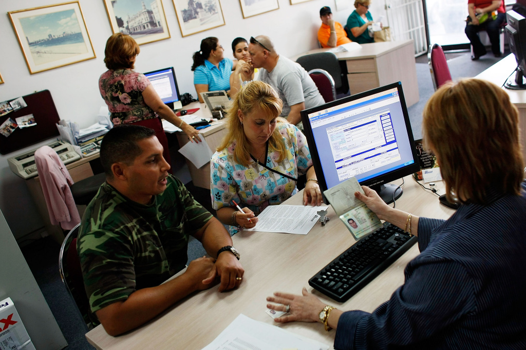 Omar Garcia (L) and Giselle Bordin purchase tickets to Cuba from travel agent Marizela Somosa in the offices of Marazul Charters on April 13, 2009 in Miami, Florida.