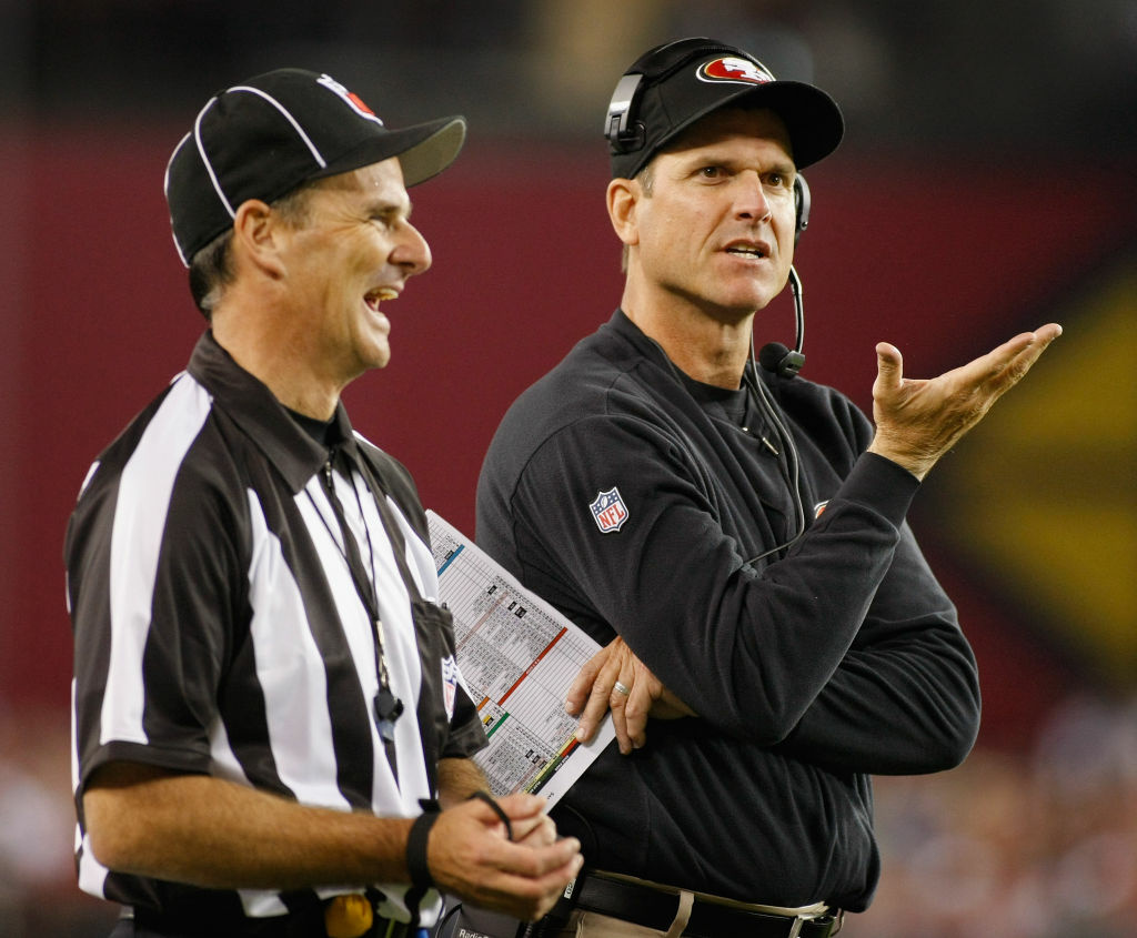 Head coach Jim Harbaugh of the San Francisco 49ers gets a laugh from Field Judge Jim Quirk during an NFL game against the Arizona Cardinals at University of Phoenix Stadium on October 29, 2012 in Glendale, Arizona.