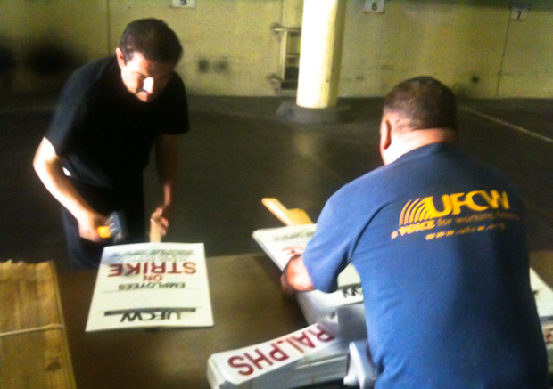 UFCW employees Jose Cruz (left) and Armando Espinoza prepare picket signs.