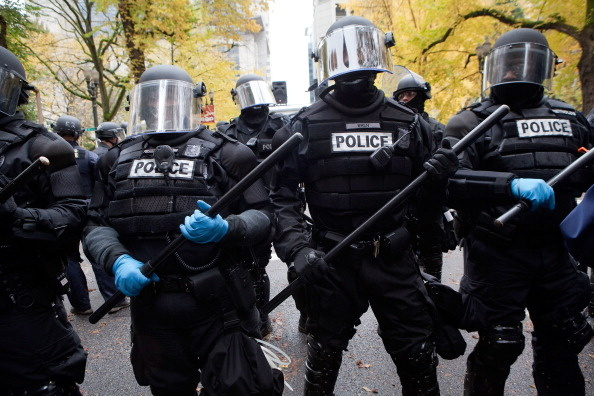 Police in riot gear with batons stand their ground near the Occupy Portland encampment Nov.13, 2011, in Portland, Oregon. Portland police have reclaimed the two parks in which occupiers have been camping after a night of brinksmanship with protesting crowds of several thousands.