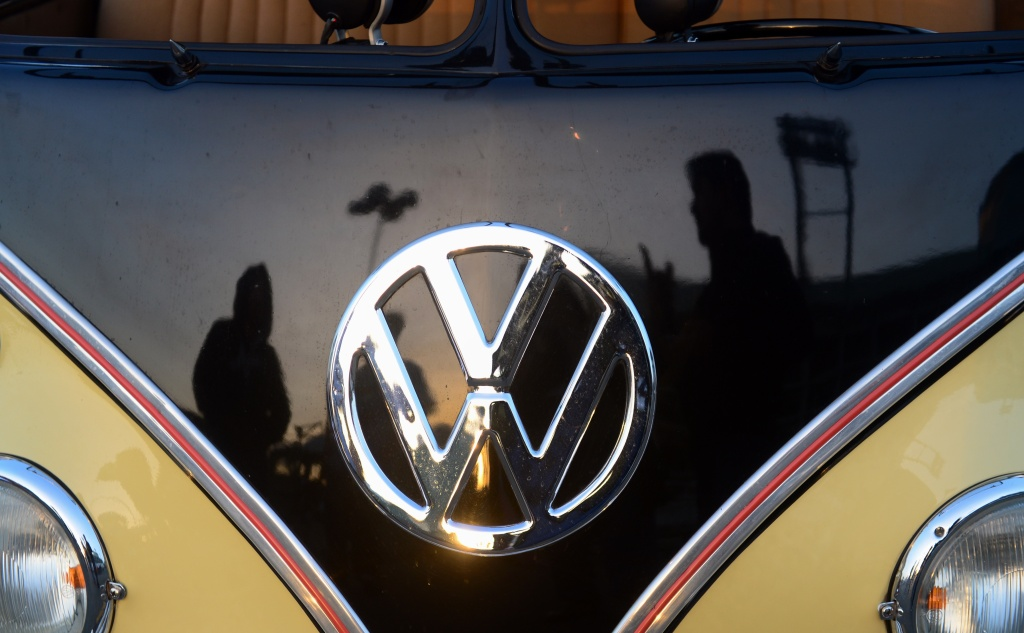 People reflected in a refurbished 1959 Volkswagen Kombi, discuss cars at 'Das O.C.T.O. Fest 2013', a swap and display gathering for enthusiasts and owners of 1967 and earlier models of the classic vehicle in Long Beach, California on October 12, 2013.