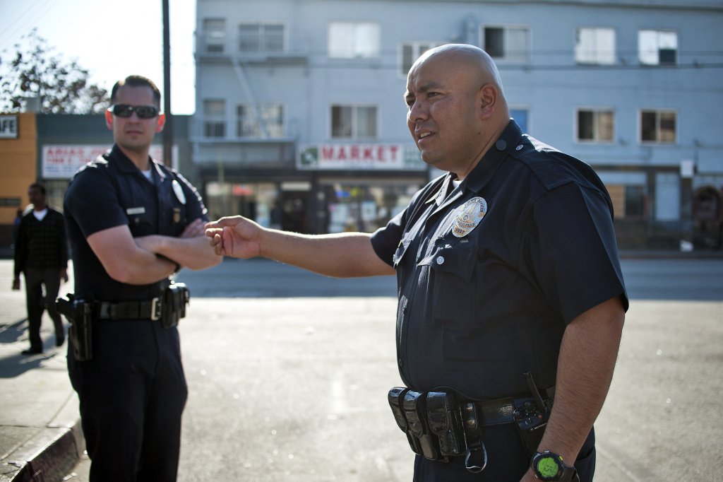 File: LAPD Officers William Allen, left, and Guillermo Espinoza talk with two people in an argument on the street. Allen and Espinoza are part of LAPD's central station where the body cameras will be tested out for 90 days. LAPD announced Tuesday that they they plan to move forward and use Taser body cameras that offer a cloud-based video storage system.