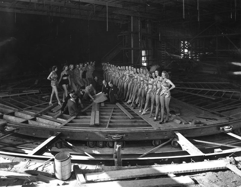 This photo shows Earl Carroll, some of his aides and chorus girls examining the theater's unique moving stage in 1938.