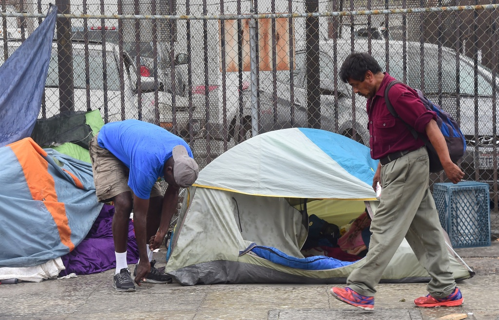 A homeless man sets up his tent along a street in Los Angeles, California on August 25, 2015. According to a report released today by the Economic Roundtable, a nonprofit research group in Los Angeles, some 13,000 people tumble into homelessness every month in Los Angeles County, where the latest official count of the homeless found 44,000 people living along county streets during a three-day period in January, a increase of 12%  in two years.  AFP PHOTO /FREDERIC J.BROWN        (Photo credit should read FREDERIC J. BROWN/AFP/Getty Images)