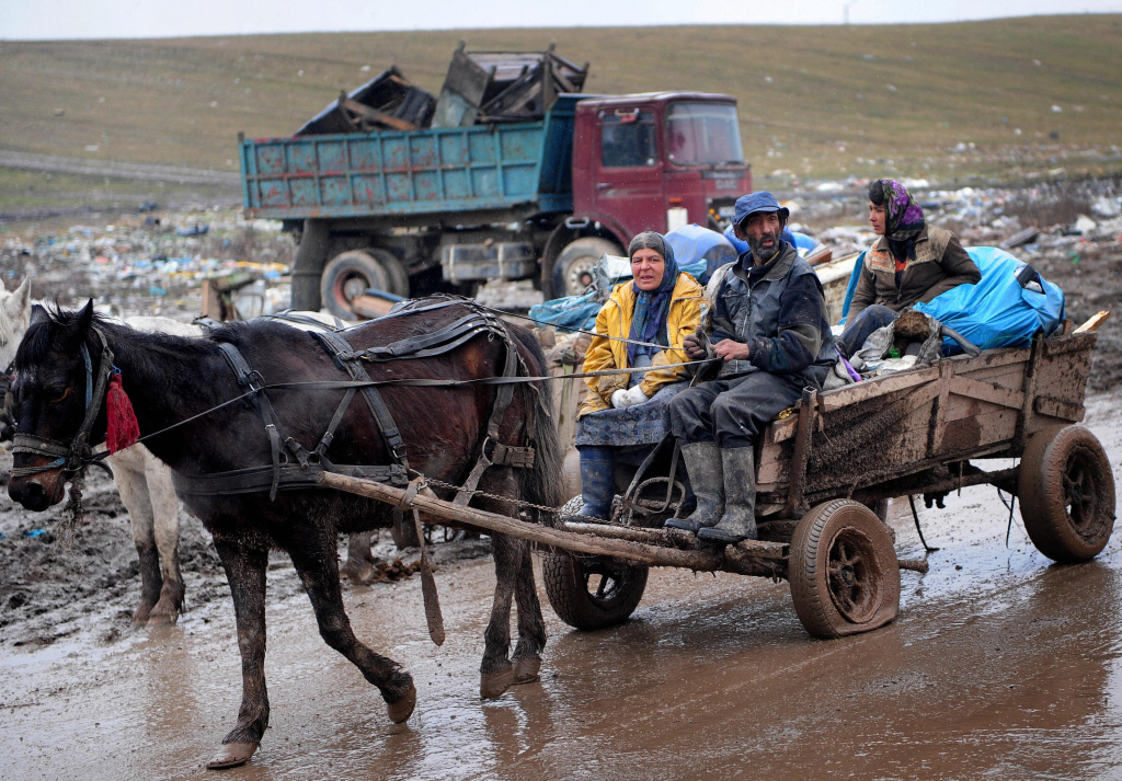 A Roma family rides a cart loaded with scrap metal to be sold as they get out from Pata-Rât city dump in northwestern Romania.