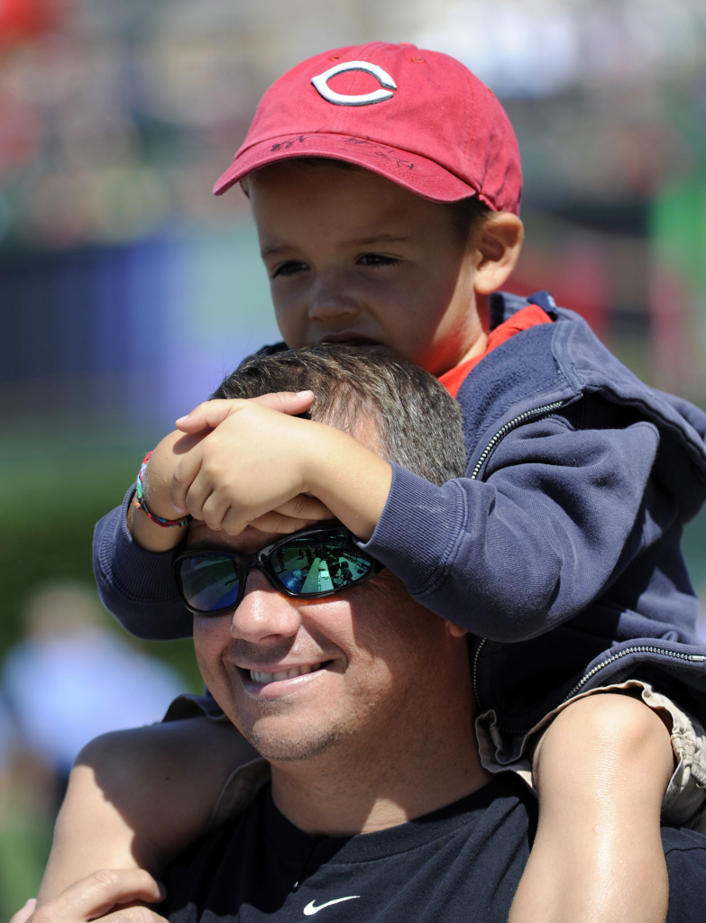 A father and son watch batting practice before the start of the game between the Chicago Cubs and the Cincinnati Reds on August 11, 2012 at Wrigley Field in Chicago, Illinois.