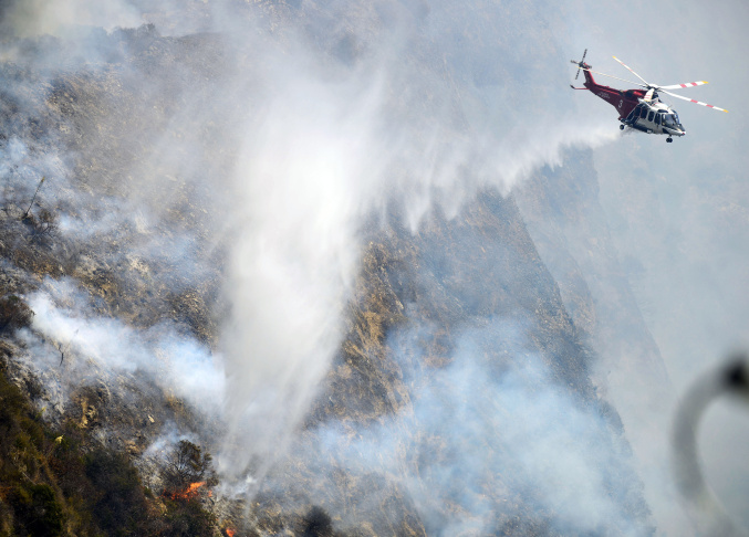 A Los Angeles City Fire Department helicopter makes a water drop on the Brand Fire Sunday afternoon.