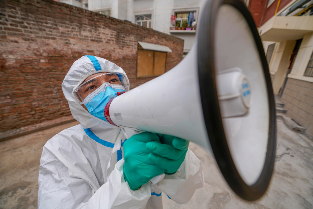 Volunteer Ekebar Emet, a 21-year-old student, publicizes epidemic prevention measures in Urumqi in northwest China's Xinjiang region on Aug. 3. His messaging reaches an estimated 78 households each day.