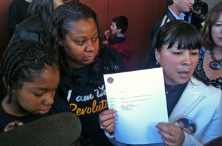 Compton Unified parent Ismenia Guzman, on right, holds receipt given by school district for petitions to turn McKinley Elementary into a charter school under California's new parent trigger law. Celerity Educational Group would run the campus as a charter if the petitions are approved.