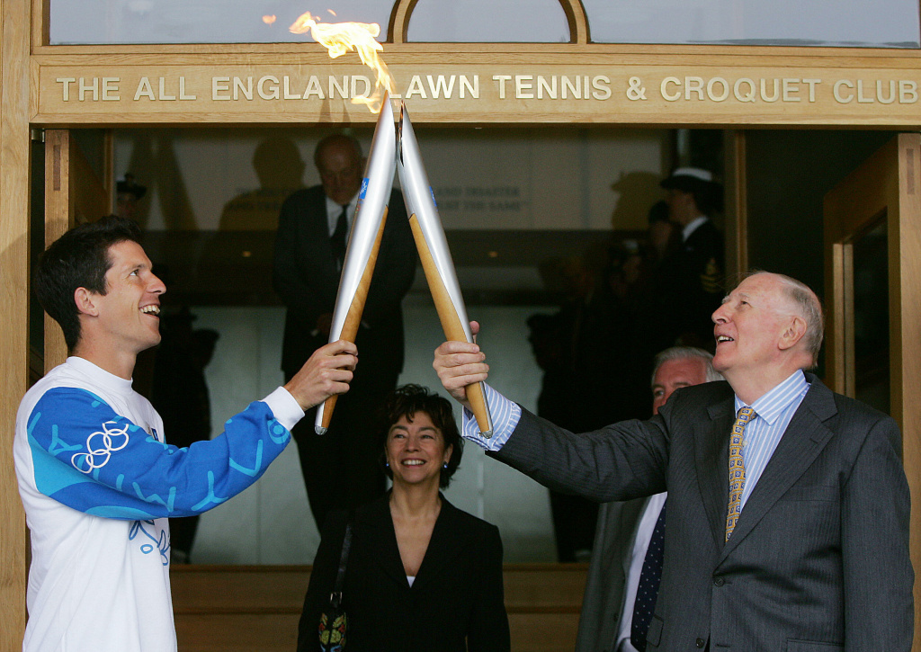 Tennis player Tim Henman (L) of Great Britain has receives the Olympic flame from Sir Roger Bannister after a lighting ceremony on the Centre Court of Wimbledon in London, 26 June, 2004.