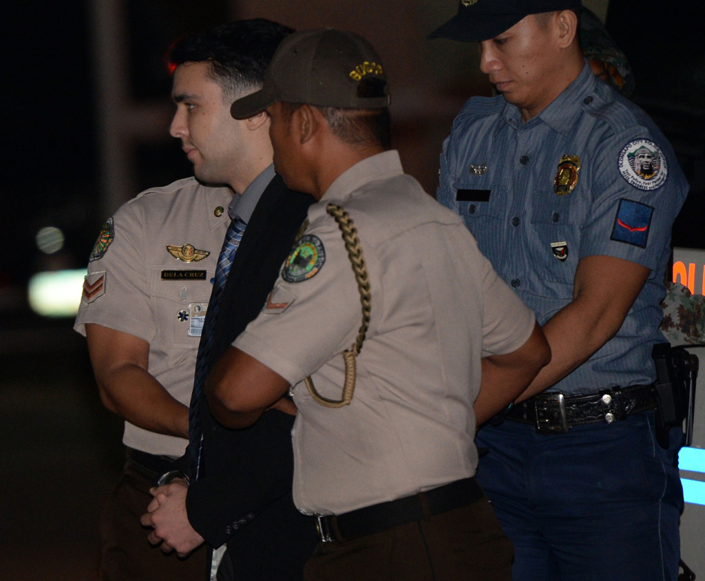 US Marine Lance Corporal Joseph Scott Pemberton (center) is escorted by a policeman and bureau of corrections official shortly after arriving at Camp Aguinaldo in Quezon City on December 1, 2015, from Olongapor city where a court convicted of him of homicide for the killing of Jennifer Laude in a motel in October 2014.