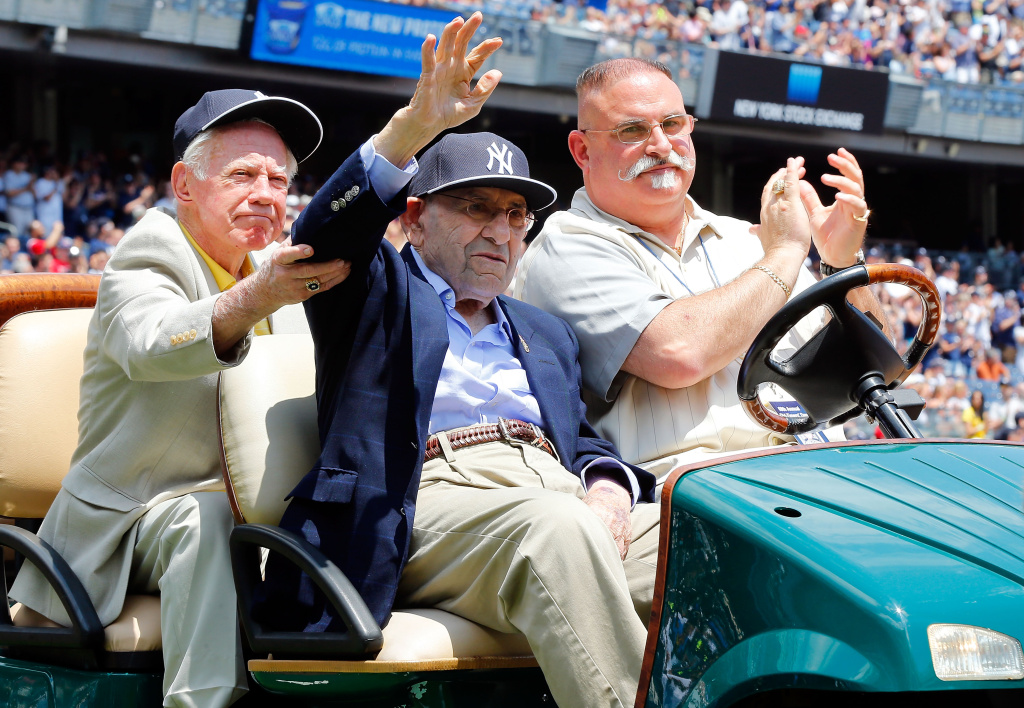 With help from former teammate New York Yankee Whitey Ford (L),  former New York Yankee Yogi Berra (C) is introduced during the teams Old Timers Day prior to a game between the New York Yankees and the Baltimore Orioles at Yankee Stadium on June 22, 2014.
