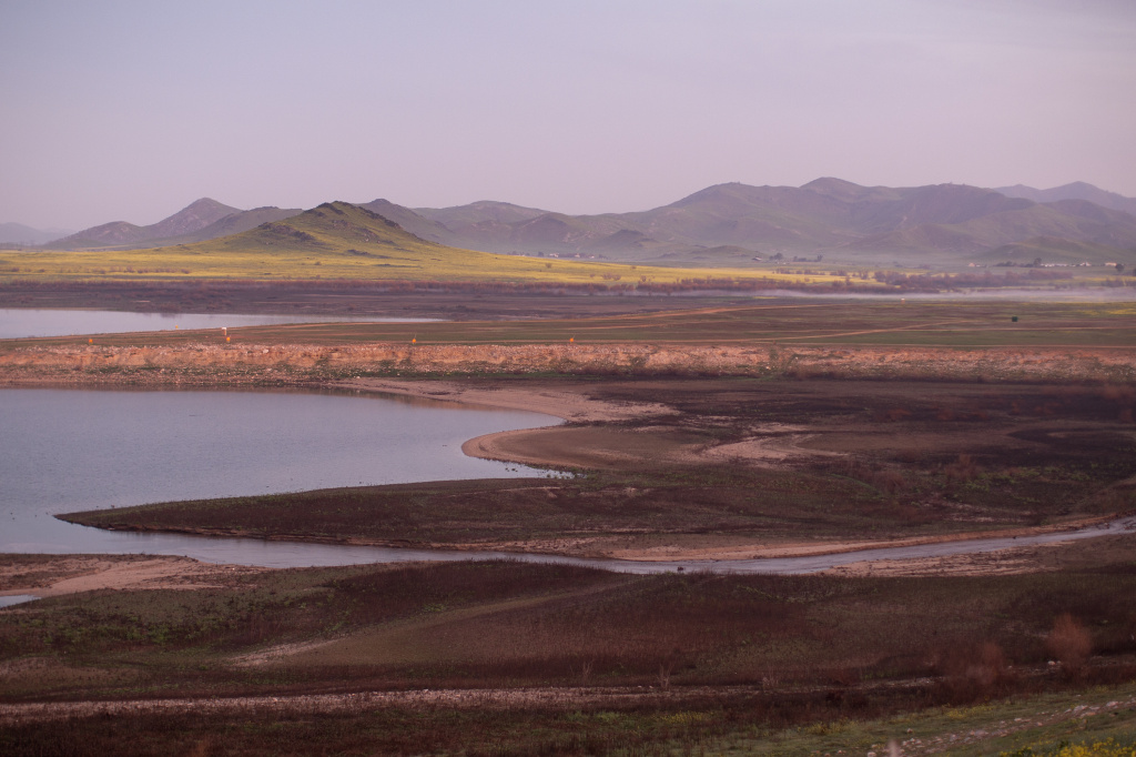 Foliage and flowers the extremely low waters of Lake Success in the wake of recent storms but rain totals remain insufficient to break the worsening drought on February 11, 2015 near East Porterville, California.