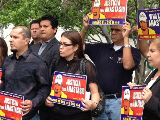 "Family members and activists, including Jose Gutierrez (far left), protest outside a federal building downtown supporting the ""Todos Somos Anastasio"" campaign."