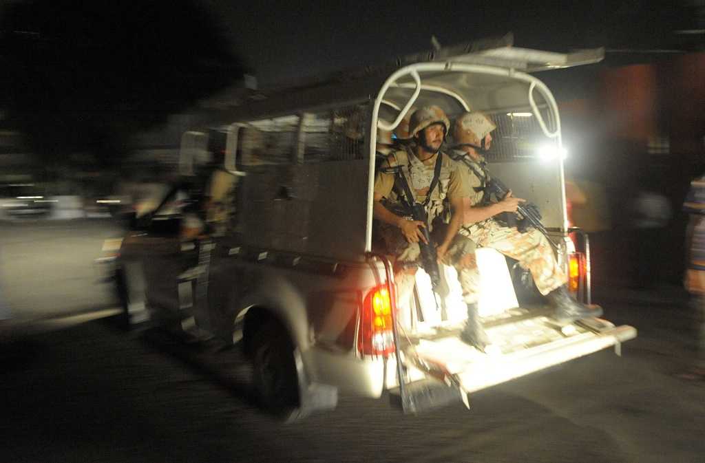 Pakistani paramilitary soldiers rush into the Karachi airport terminal after the militants' assault in Karachi on June 9, 2014. Heavily armed militants attacked Pakistan's busiest airport in the southern city of Karachi Sunday night, killing at least five people as flights were suspended and the army was called in, officials said.