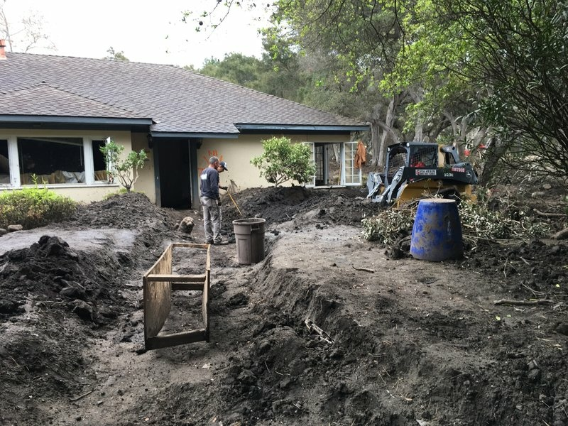 John Trimble, foreground, and other volunteers cut a path to the front door of Peri Thompson's home.