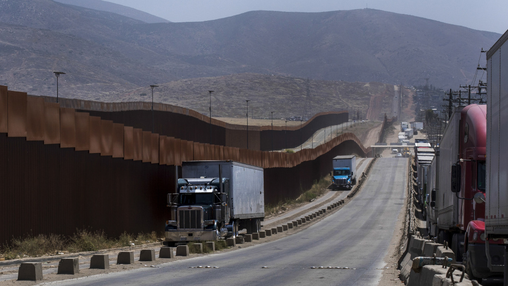 Trucks pass along a border wall as they get into position to cross into the United States at the border in Tijuana, Mexico, on Friday. Companies have been rushing to ship as many goods as possible out of Mexico to get ahead of possible tariffs threatened by President Donald Trump, hurriedly sending cars, appliances and construction materials across the border to beat Monday's deadline.