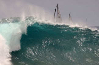 Boats sail past big waves at The Wedge as a winter storm with 50-knot winds in the Southern Hemisphere off Tahiti generates high surf at south-facing southern California beaches on July 24, 2009 in Newport Beach, California.