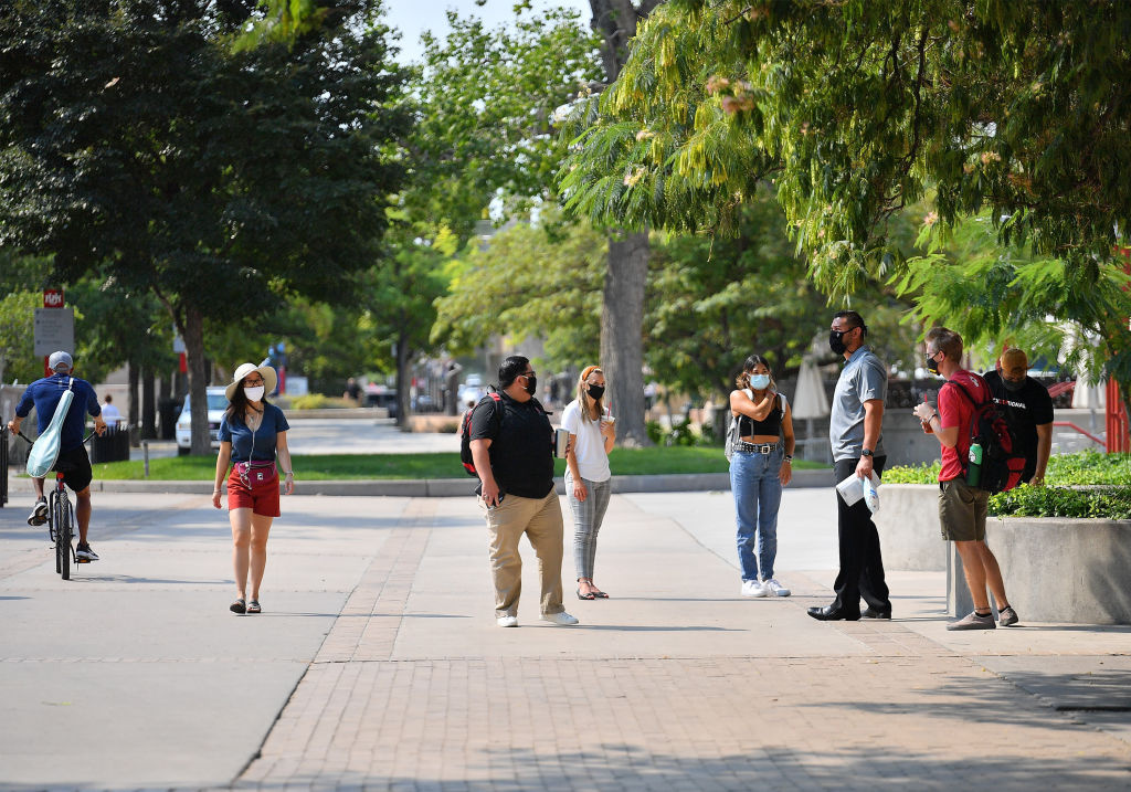 Jose Villar talks to students while they walk on campus as classes begin amid the coronavirus (COVID-19) pandemic on the first day of the fall 2020 semester at the University of New Mexico on August 17, 2020 in Albuquerque, New Mexico.