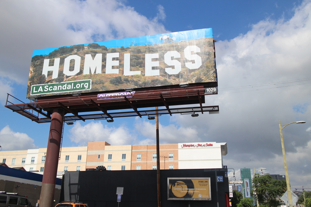 This billboard at the corner of Vine St. and Santa Monica Blvd. in Hollywood, is one of more than a dozen that went up around Los Angeles over the weekend. Out on the street, the real Hollywood can be seen in the distant.