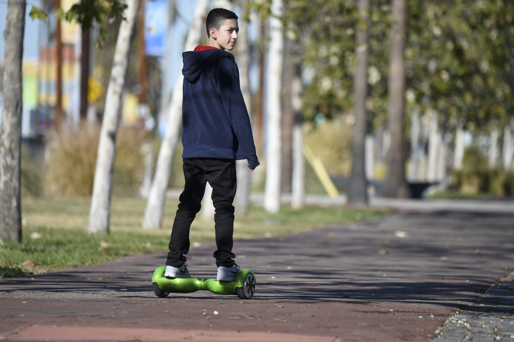 A boy rides a hoverboard on the day after Christmas, in San Pedro, California December 26, 2015. Reports of some hoverboards, also known as self-balancing, two-wheeled scooters catching fire have led to an investigation by the Consumer Product Safety Commission.  AFP PHOTO / ROBYN BECK / AFP / ROBYN BECK        (Photo credit should read ROBYN BECK/AFP/Getty Images)