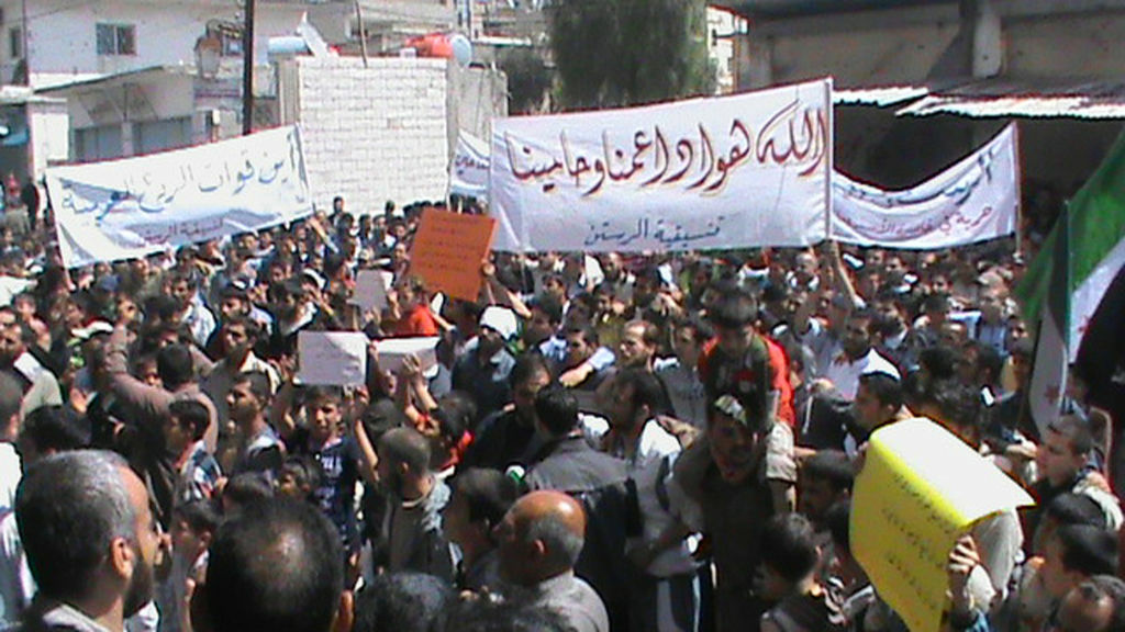 A picture taken by a mobile phone on April 13, 2012 shows Syrian protesters holding slogans during an anti-regime demonstration in the city of Rastan near the flashpoint city of Homs.