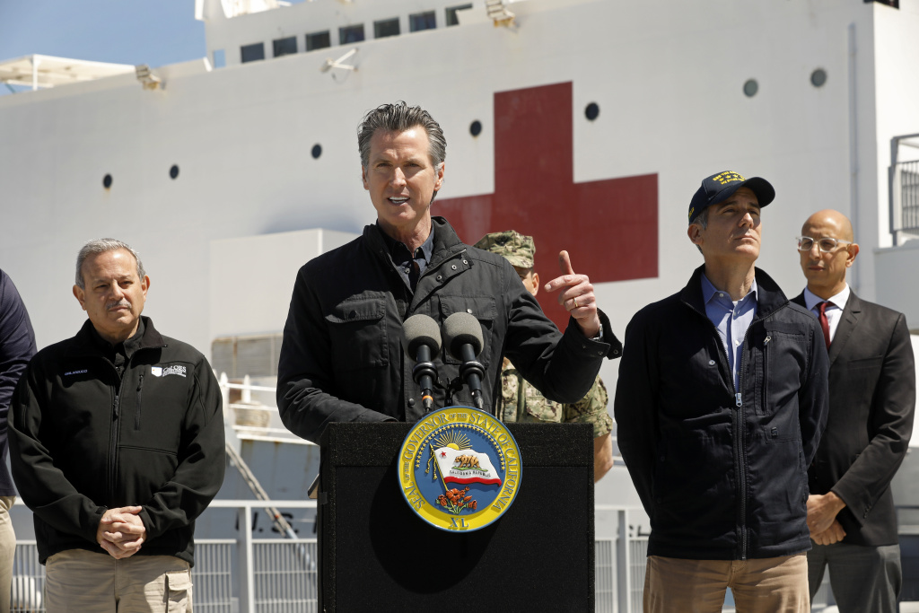 LOS ANGELES, CA - MARCH 27: California Governor Gavin Newsom speaks in front of the hospital ship USNS Mercy that arrived into the Port of Los Angeles on Friday, March 27, 2020,  to provide relief for Southland hospitals overwhelmed by the coronavirus pandemic. Also attending the press conference were Director Mark Ghilarducci, Cal OES,  left, Los Angeles Mayor Eric Garcetti, second from right, and Dr. Mark Ghaly, Secretary of Health and Human Services, far right, along with others not shown. (Photo by Carolyn Cole-Pool/Getty Images)