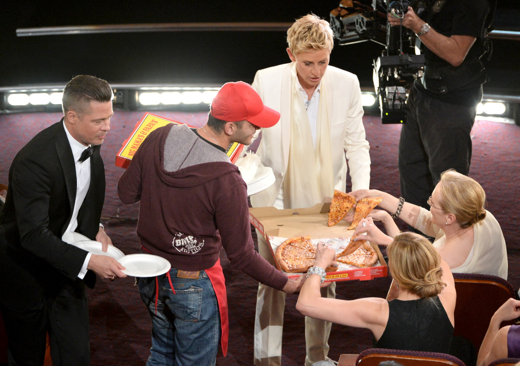 Host Ellen DeGeneres (C) with actor Brad Pitt (L) and actress Meryl Streep in the audience while passing out pizza during the Oscars at the Dolby Theatre on March 2, 2014 in Hollywood, California.
