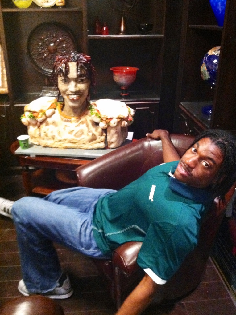 Robert Griffin III, a likely draft pick in the NFL Draft, pictured with a giant sandwich trophy based on his likeness.