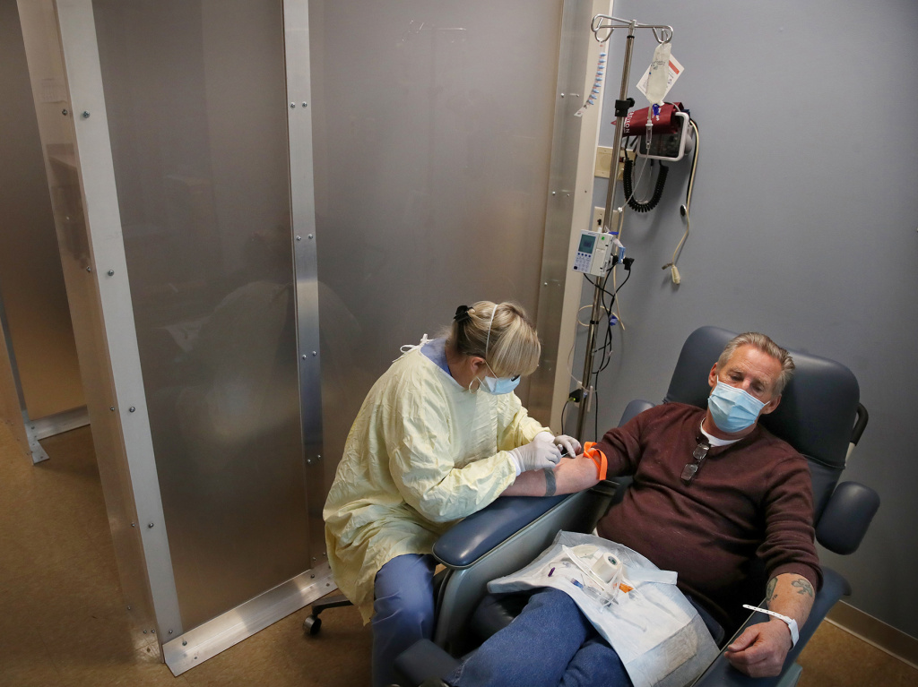 Nurse Janet Gilleran prepares to treat COVID-19 patient Mike Mokler with bamlanivimab, a monoclonal antibody drug from Eli Lilly, at the Respiratory Infection Clinic of Tufts Medical Center in Boston on Dec. 31, 2020.