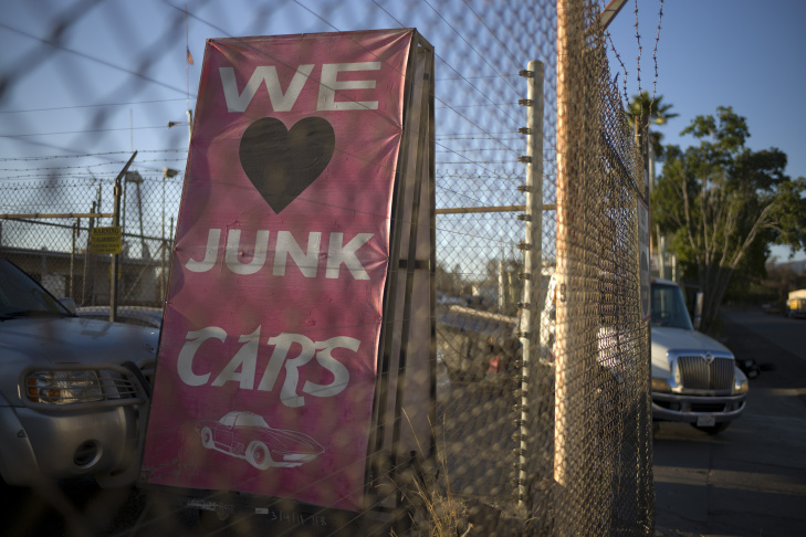 In this Wednesday, Nov. 11, 2015 photo, a man walks between junk cars at Aadlen Brothers Auto Wrecking, also known as U Pick Parts, in the Sun Valley section of Los Angeles. It's not just a junkyard or even a really big junkyard, but a living, breathing monument to Los Angeles pop culture. But the family business is closing on New Year's Eve, and everything must go by then, the cars, the shark, the arches, even the giant car-crushing machine.