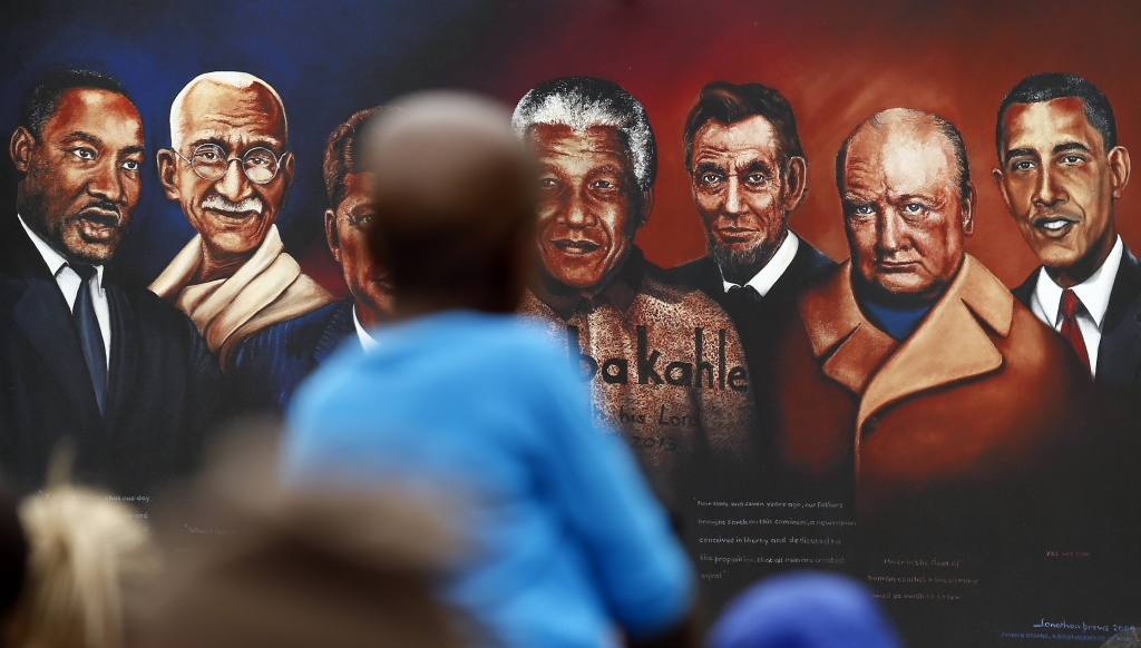 A painting with , left to right, Martin Luther King, Mahatma Gandhi , John F. Kennedy, Nelson Mandela, Abraham Lincoln, Winston Churchill, and Barack Obama, outside the home of former president Nelson Mandela in Johannesburg, South Africa, Monday, Dec. 9, 2013. Scores of heads of state and government and other foreign dignitaries, including royalty, are beginning to converge on South Africa as the final preparations for Tuesday's national memorial service for liberation struggle icon Nelson Mandela are put in place. (AP Photo/Themba Hadebe)