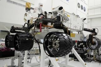 Engineers finish installing six new wheels on the Curiosity rover, and rotate all six wheels at once on July 9, 2010, at NASA's Jet Propulsion Laboratory in Pasadena, Calif.
