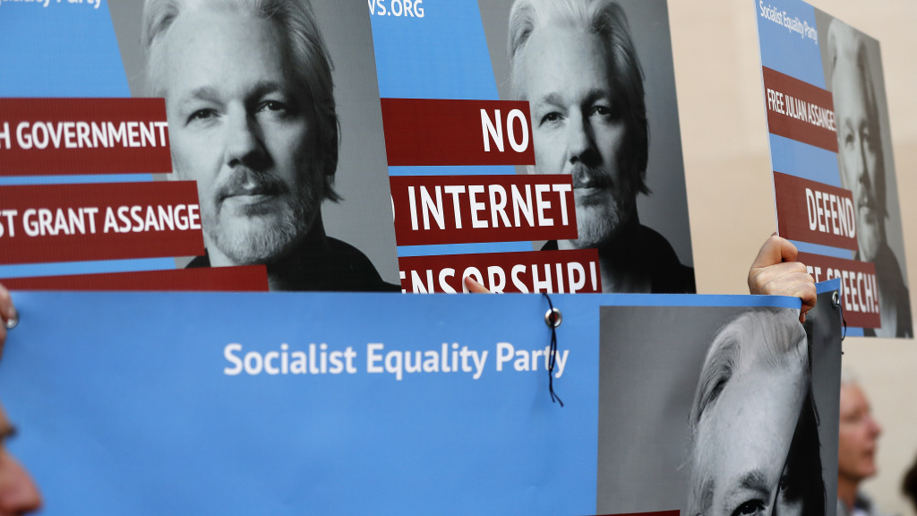 Protesters carry posters depicting Julian Assange outside Westminster Magistrates Court in London on Thursday where the WikiLeaks founder appeared by video link from prison for an extradition hearing.