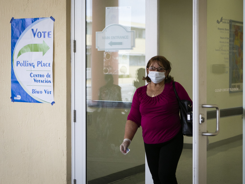 A woman wearing a mask and protective gloves leaves after casting her vote in the Florida Democratic primary election in Miami on March 17.